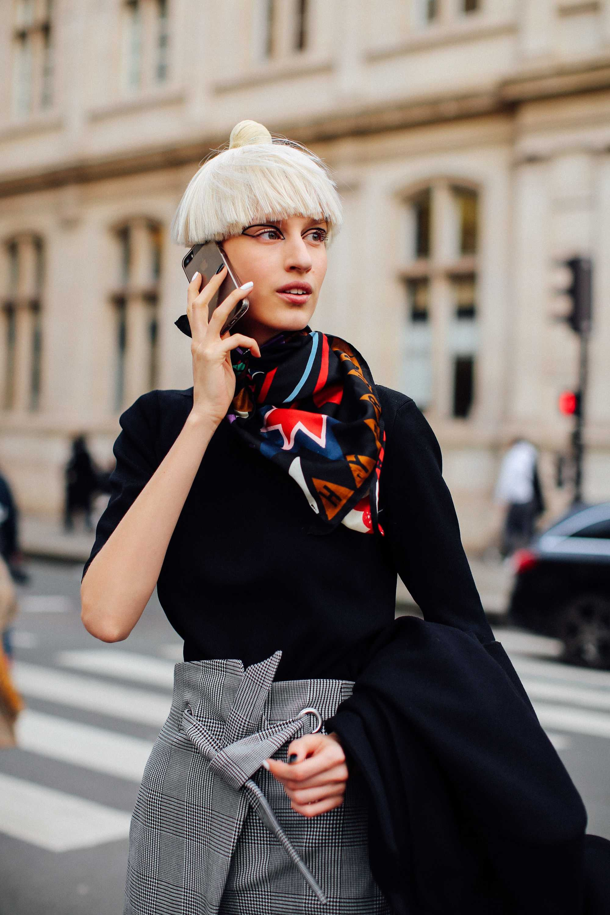 Girl with white blonde mushroom hair cut outside on the phone