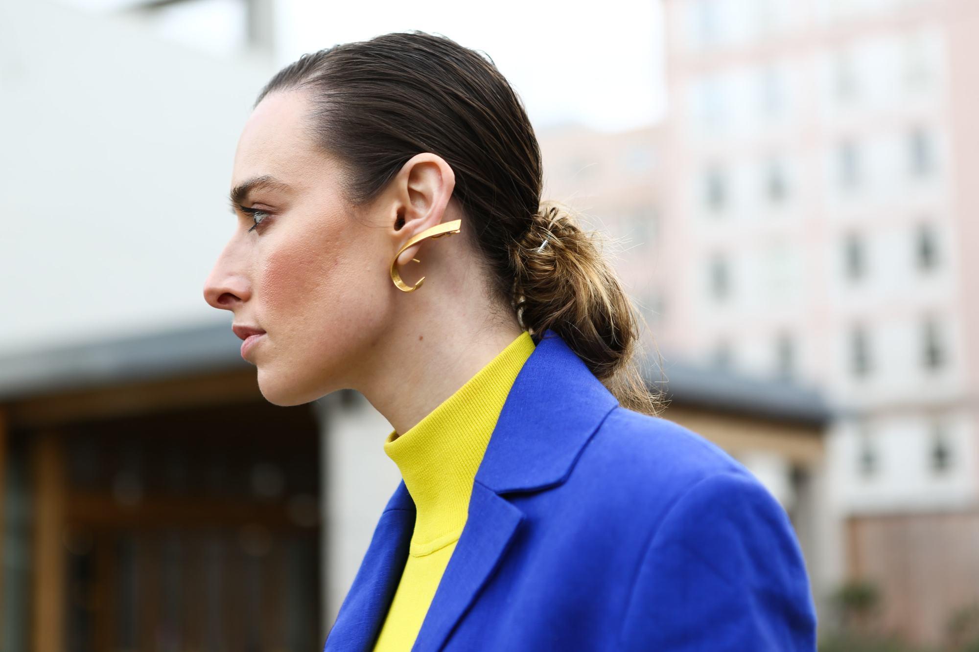 Side profile of brunette woman with low bun outside