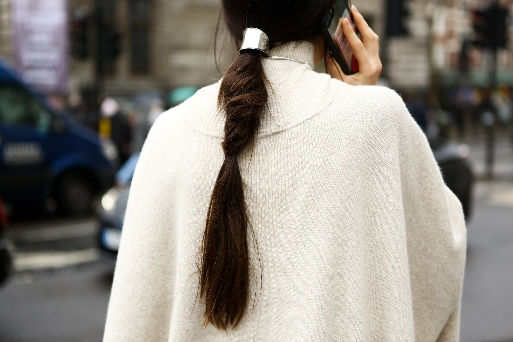 Brunette woman with low ponytail on the phone outside fashion week