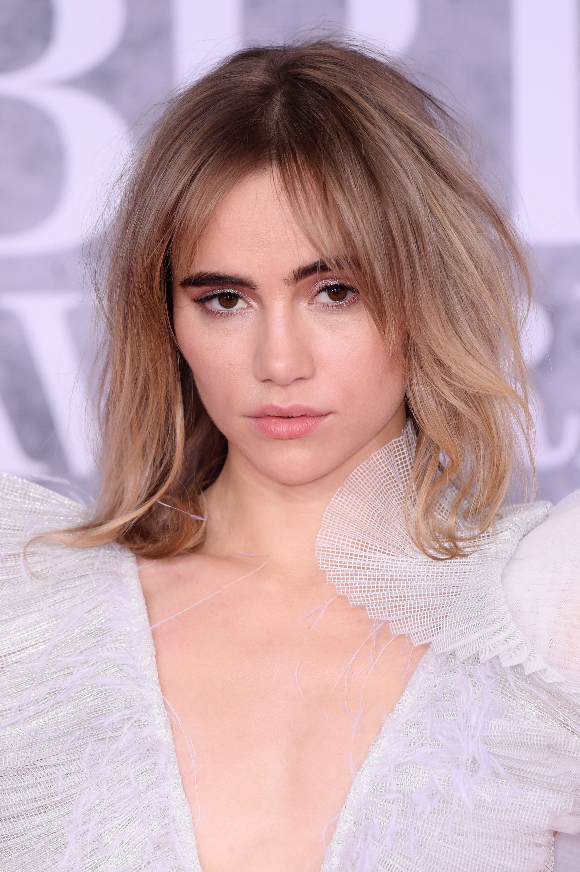 Spring haircuts: Suki Waterhouse at the 2019 Brit Awards with mid-length bronde shaggy layered hair, wearing a ruffled dress
