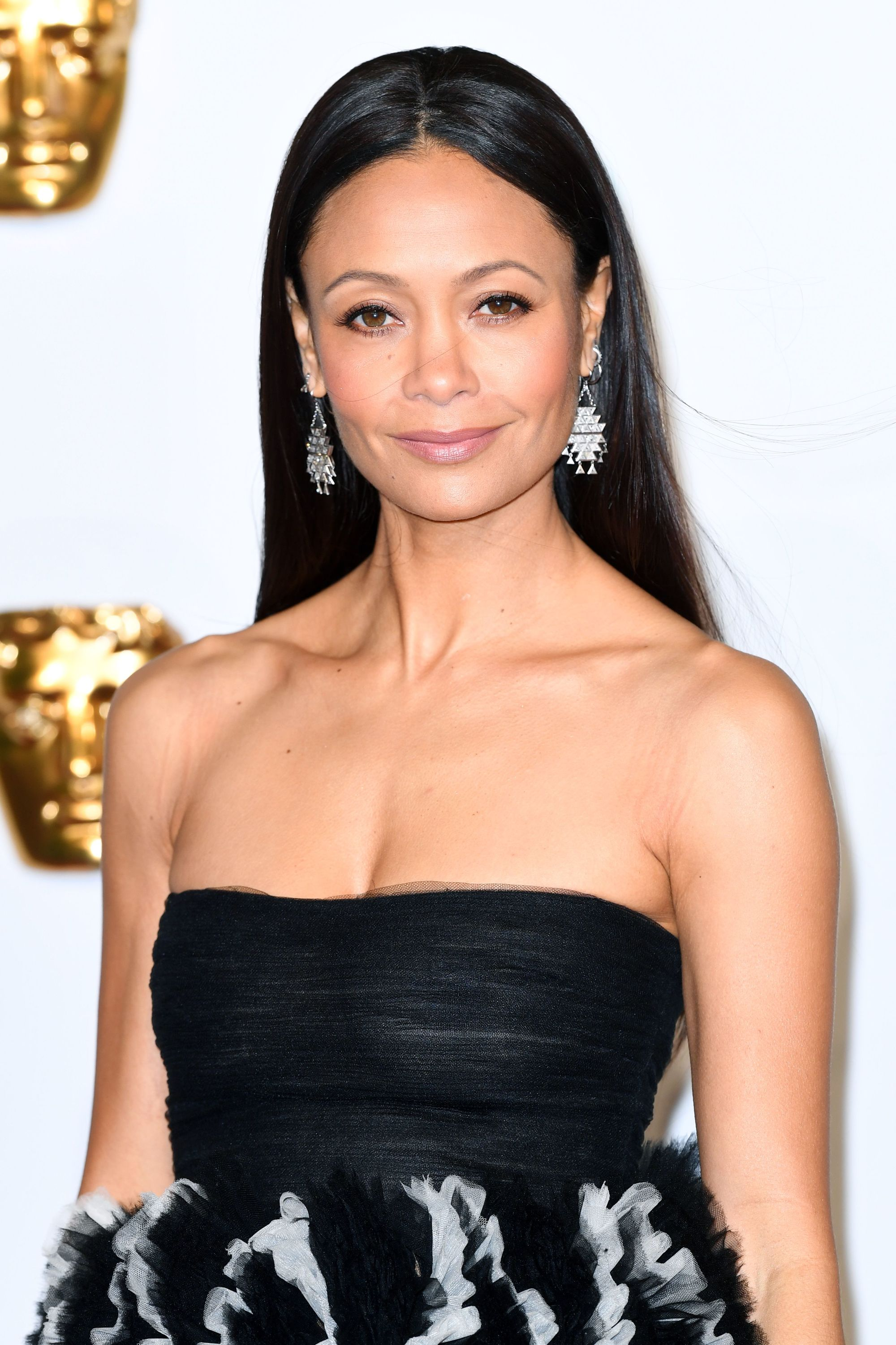 BAFTAs hairstyles: Thandie Newton with long straight dark brown hair wearing a black strapless dress and drop earrings on the red carpet.