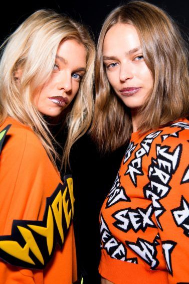 Thickening shampoo products guide: Two models backstage with short and medium wavy, volumised hair wearing slogan jumpers backstage