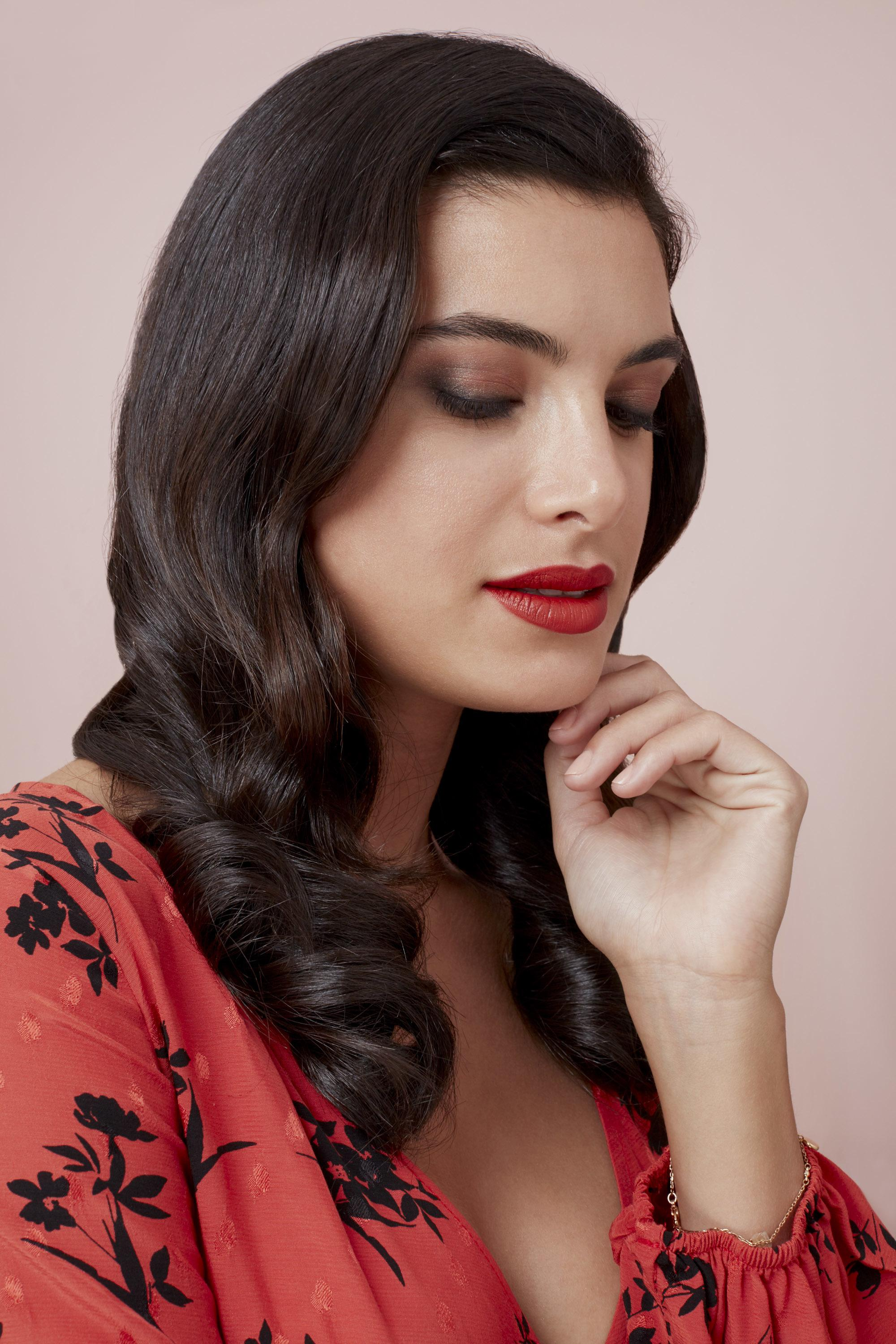 Valentines hair: Brunette woman with polished Hollywood waves, wearing a red floral dress and red lipstick