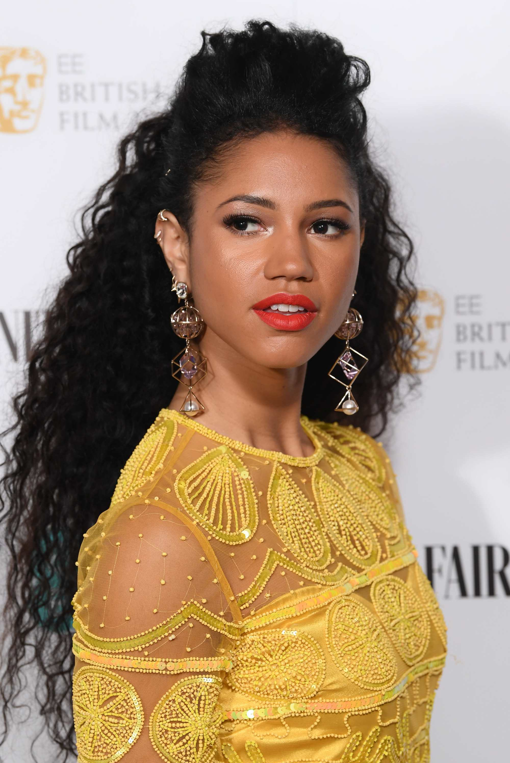 Celebrity Valentine's Day Hair: Side shot of Vick Hope with long dark brown curls styled into a half-up, half-down bun, wearing a yellow lace dress with swanky earrings on the red carpet