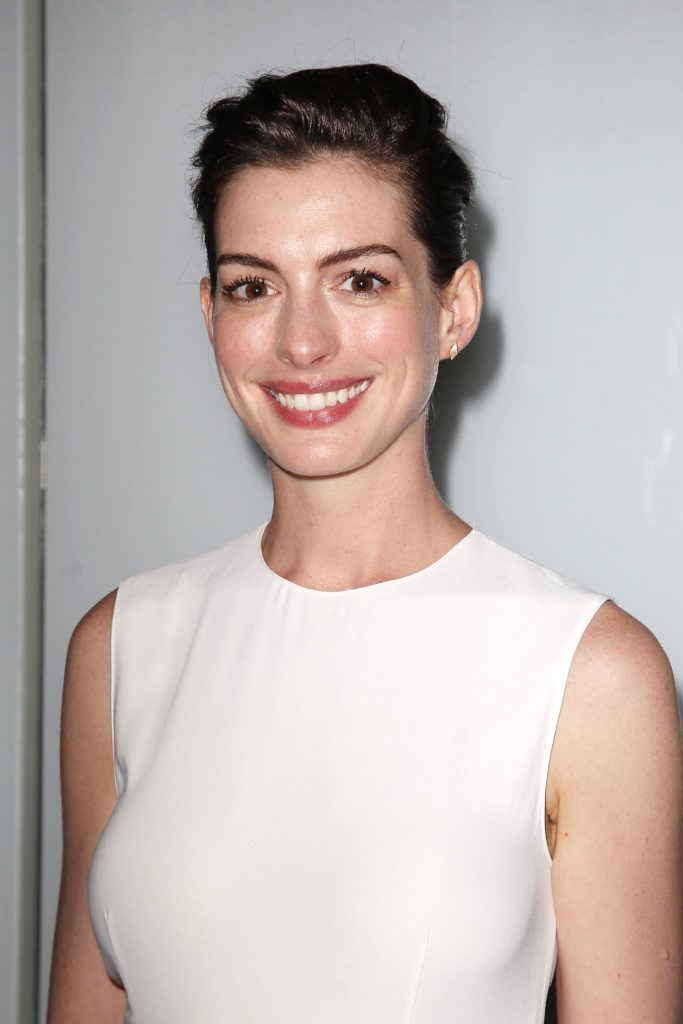 actress anne hathaway at a premiere wearing a white dress with her short brown hair in a mature swept back pixie cut hairstyle