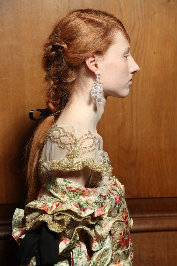 close up shot of model backstage with red hair in a braided ponytail, complete with a hair bow accessory, wearing floral gown and drop earrings