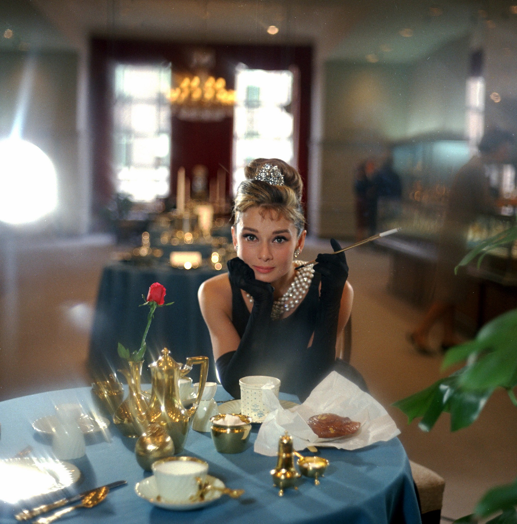 Audrey Hepburn as Holly Golightly, with beehive updo hairstyle, wearing all black with pearls and posing in a cafe