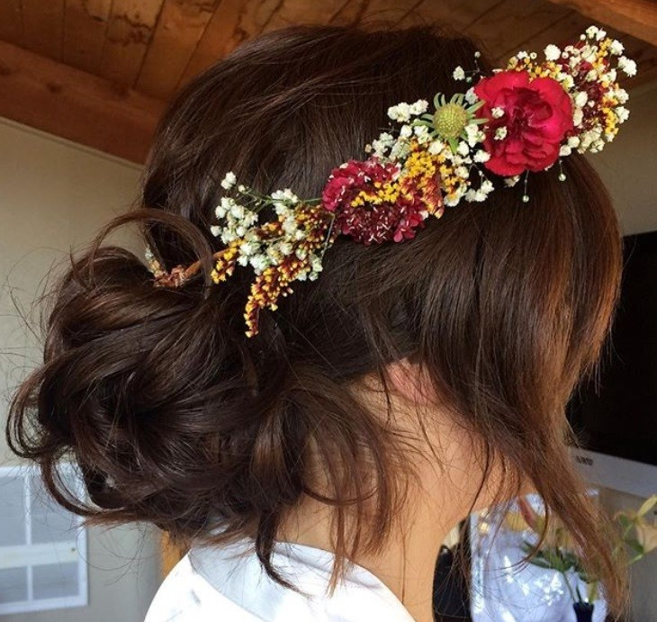 textured hairstyles: close up shot of woman with messy bun hairstyle, wearing floral crown and white dress