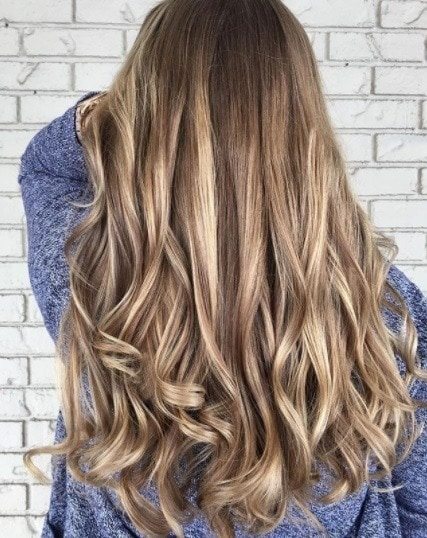 Back View Of A Woman With Blondey Brown Curled Hair Highlights And Lowlights