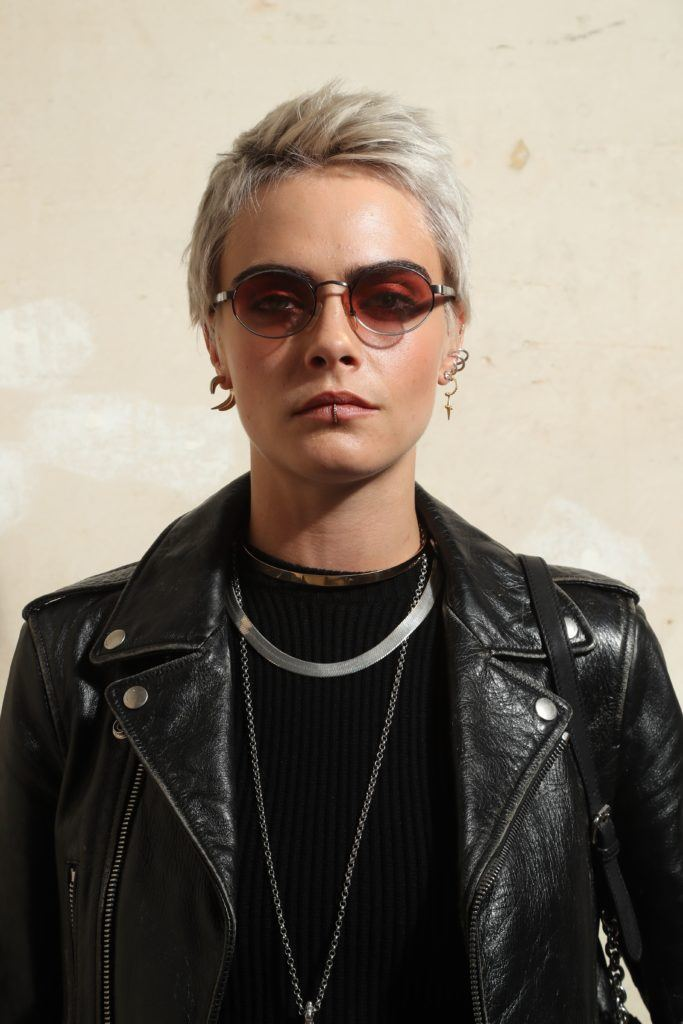 british model cara delevingne with a platinum blonde pixie cut wearing a black top and black leather jacket