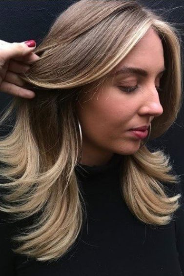 woman with chunky light brown and blonde highlights with flicked out ends