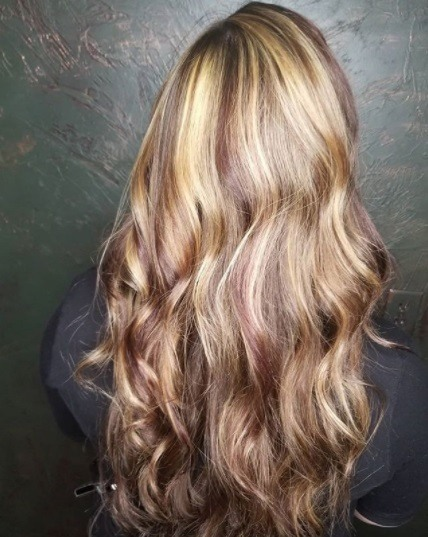 woman with long curly blonde strawberry blonde and brunette highlights