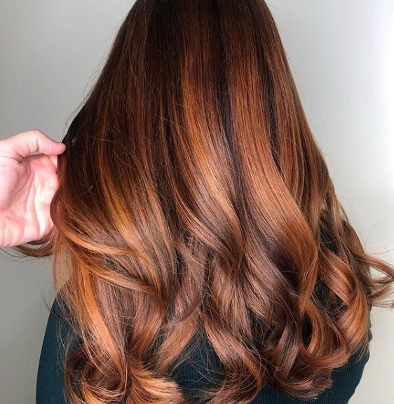 Copper highlights: Back view of a woman with long copper balayage hair, styled in soft curls