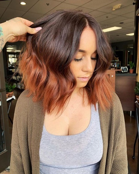 Copper highlights: Photo of a woman with a wavy brown to copper ombre bob, wearing a grey top and khaki cardigan