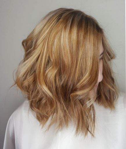 Copper highlights: woman with blonde copper highlights wavy shoulder length long bob wearing white top