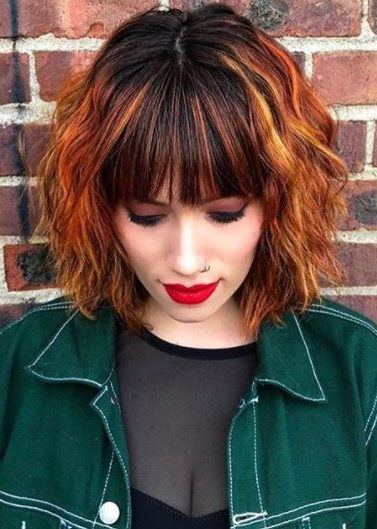 woman with wavy dark hair with copper highlights and full bangs wearing green denim jacket