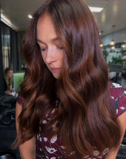 Copper highlights: woman with long dark auburn wine hair with soft copper highlights in wavy finish wearing pattern top
