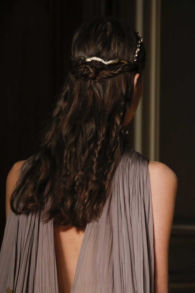 close up shot of model with half up half down rose braid, with hidden plaits, wearing silver and walking on the runway