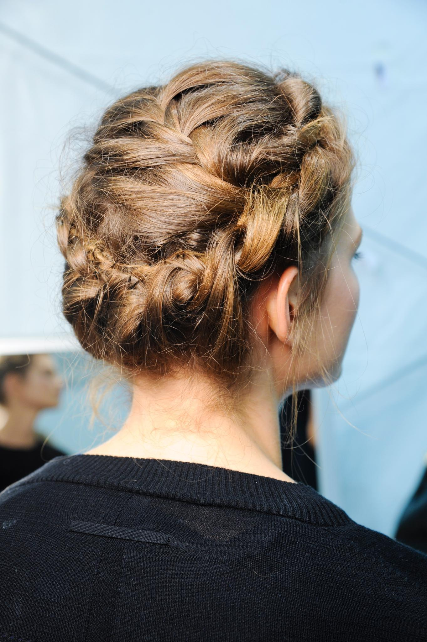 Side shot of a woman with medium brown hair styled into a crown braid updo, wearing a black top and posing backstage