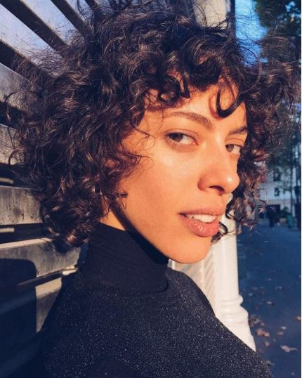 Short brown hairstyles: woman with short brown curly hair with short curly fringe