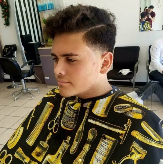 man sitting in the barbers chair with a curly taper comb over haircut