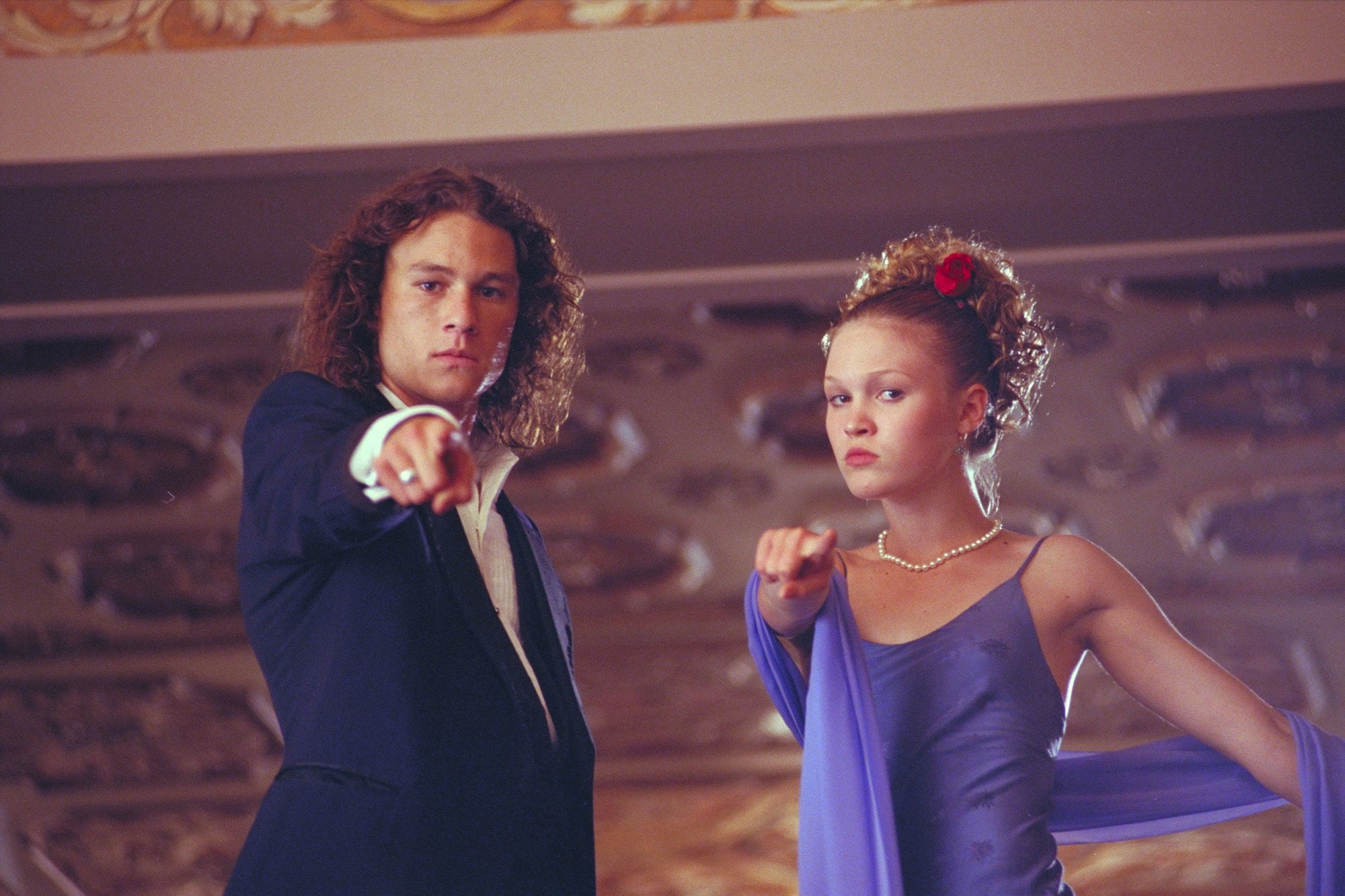 close up shot of julia stiles with curly updo hairstyle with flowers in it, wearing all purple, standing next to heath ledger on the set of 10 Things I hate about you
