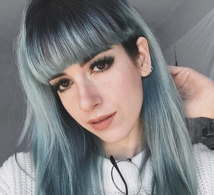 close up shot of woman with full, blunt emo bangs, wearing all white and posing on Instagram