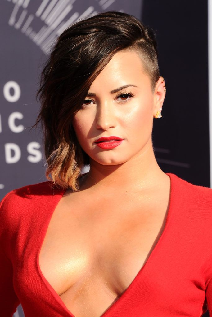 singer demi lovato on the red carpet in a plunging v neck red dress with an asymmetric undercut bob hairstyle