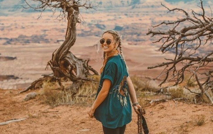 close up shot of woman at the grand canyon with boxer braids, a long top and jeans, wearing sunglasses and posing