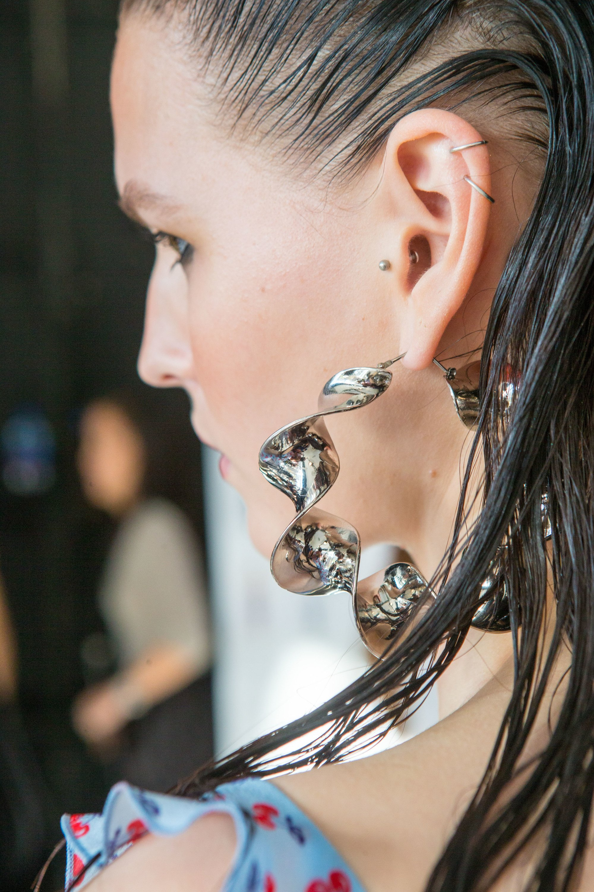 close up of a model backstage at a runway show with wet look brown straight hair combed behind her ear wearing large silver twisted earrings