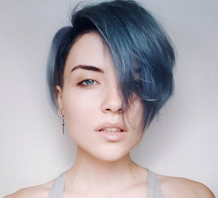 Instagram close up shot of woman with short pixie and side swept emo bangs hairstyle, wearing grey tank top and posing