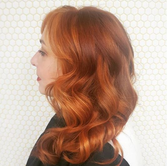 Copper highlights: side view of woman with copper highlighted medium length wavy hair wearing dark top