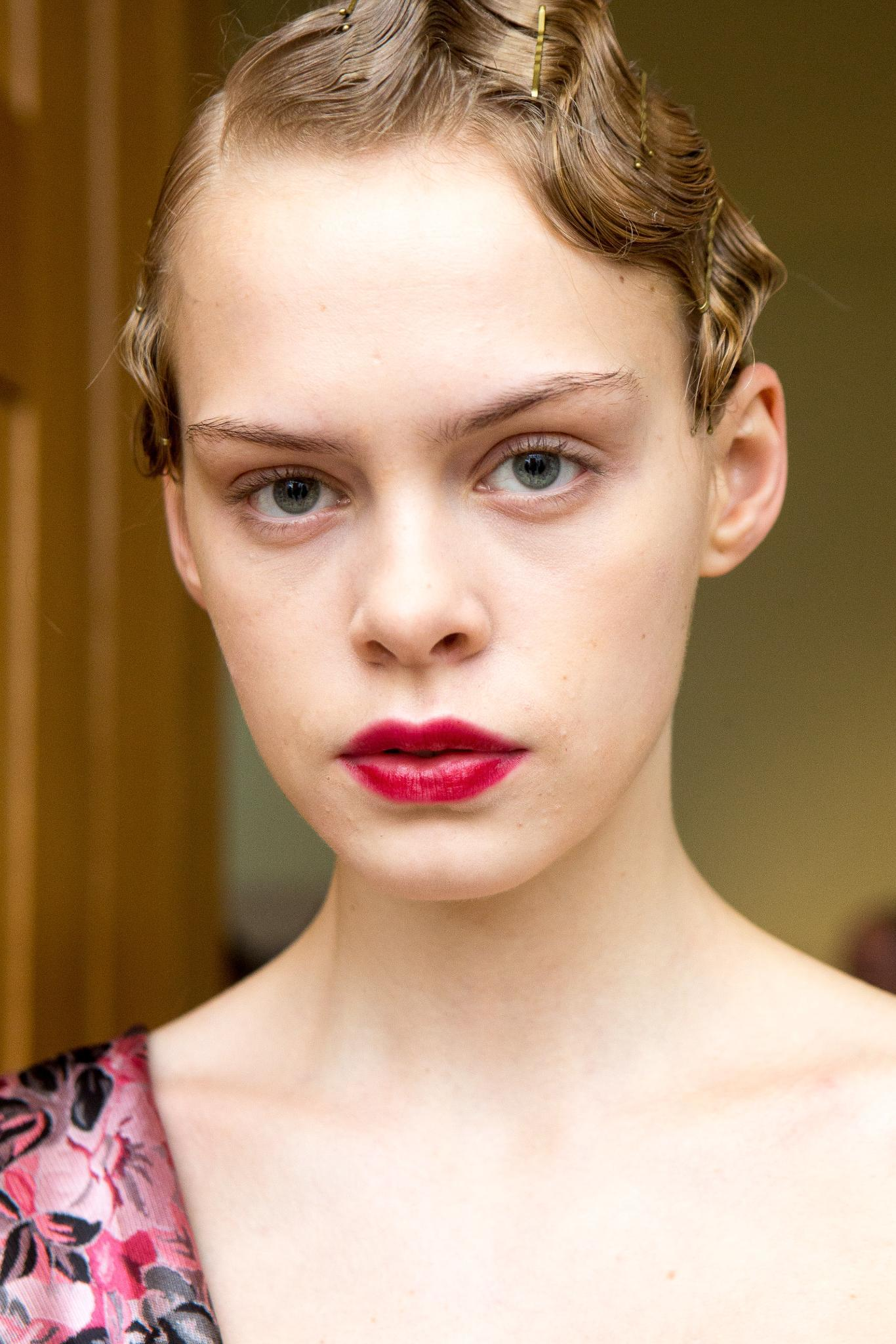 Wedding guest hairstyles: Shot of a model with her light blonde hair styled into a finger wave, wearing a cherry lip and posing backstage at a show
