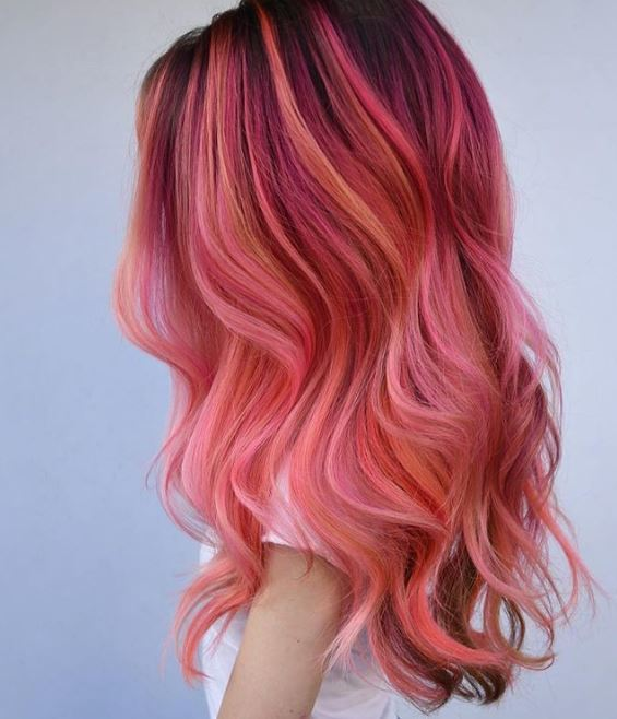 flamingo hair: side view of woman with long pink multi-toned highlighted wavy long hair