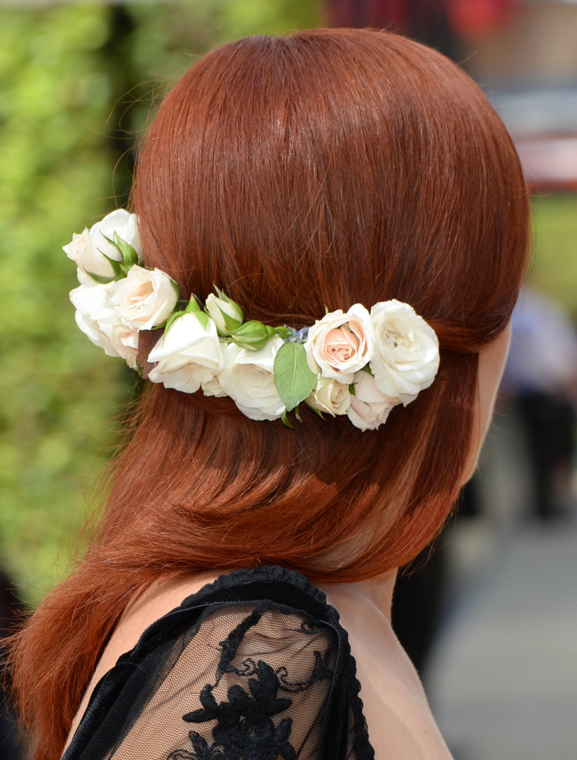 Wedding guest hair: Back shot of a woman with copper red hair styled to sleek perfection, wearing a low flower hairpin with a black netted top