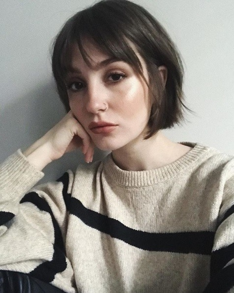 Short brown hairstyles: Woman with a brunette French girl inspired bob with bangs, wearing a cream and black striped jumper