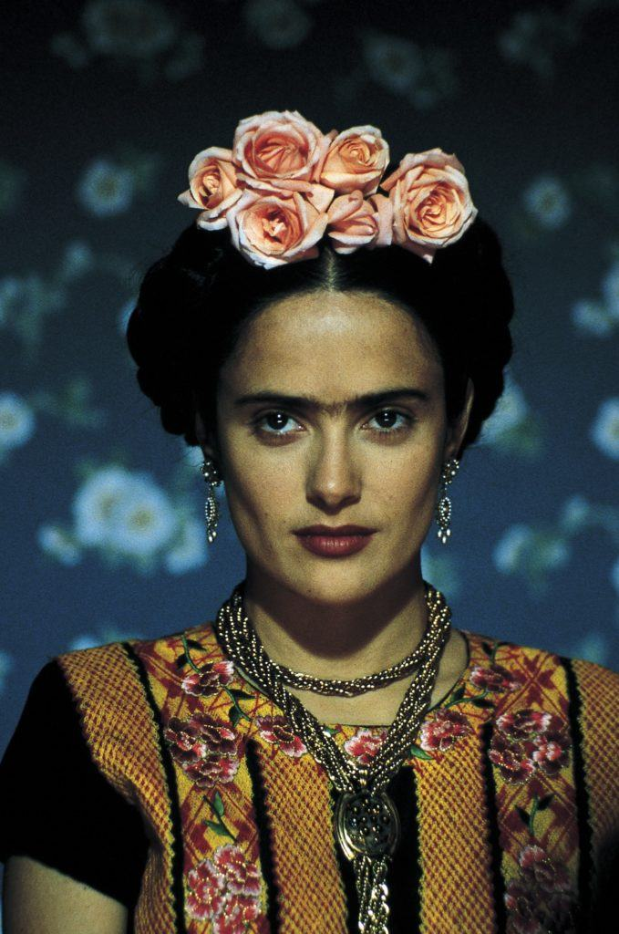 close up shot of selma hayek as frida kahlo, with milkmaid braid updo with flowers in it, wearing drop earrings and floral outfit