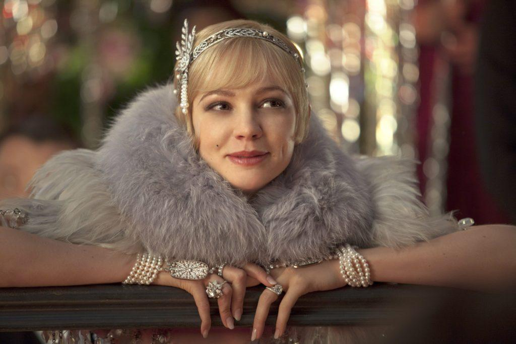 close up shot of carey mulligan as daisy buchanan, wearing a furry scarf, a flapper dress and a silver hairband hair accessory with pixie haircut, on the set of The Great Gatsby