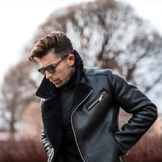 brunette man standing outside in front of a tree wearing a leather jacket and sungalsses with a grown out taper comb over hair cut