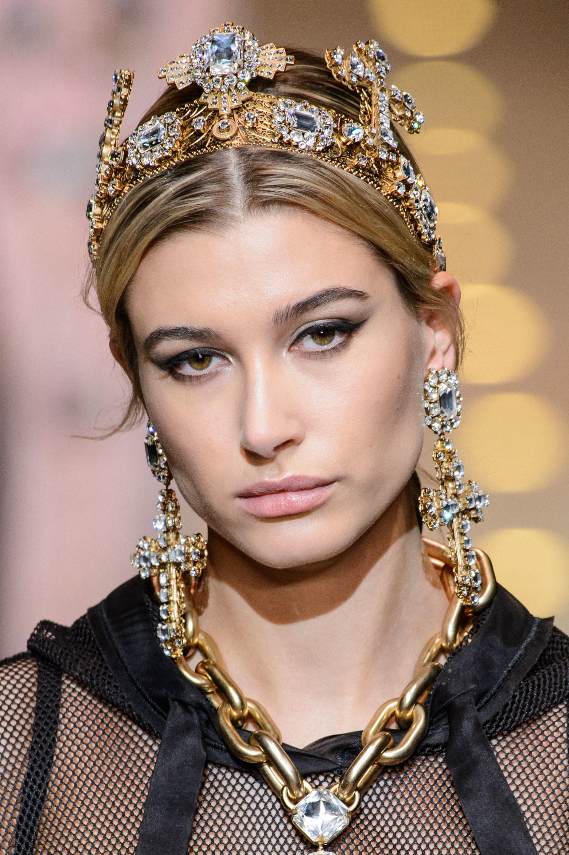 close up shot of hailey baldwin with a tiara hair accessory, wearing black lace, gold necklace and walking on the runway