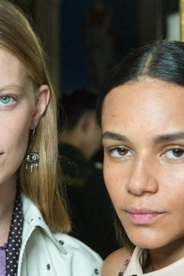 Two models backstage at the Bottega Veneta show with smooth, straight hair staring into the camera
