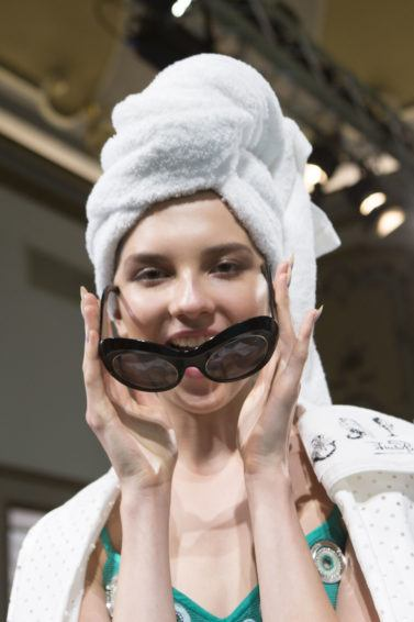 hair restoration shampoo guide: close up shot of model with printed towel on her head, wearing matching bathrobe, posing backstage at the emillio pucci SS18 show