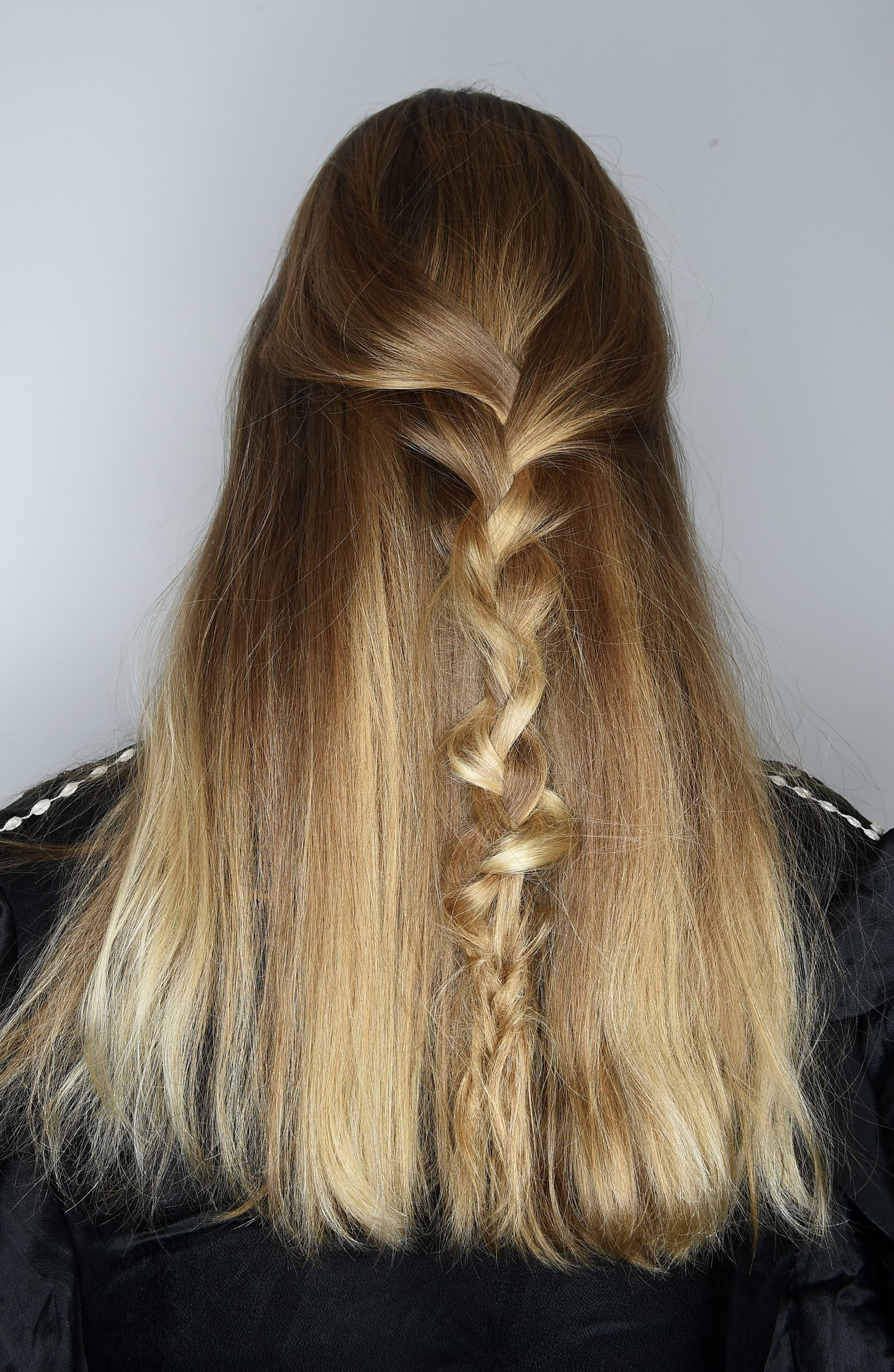 prom hairstyles: close up shot on model backstage with a half up half down twisted braid hairstyle