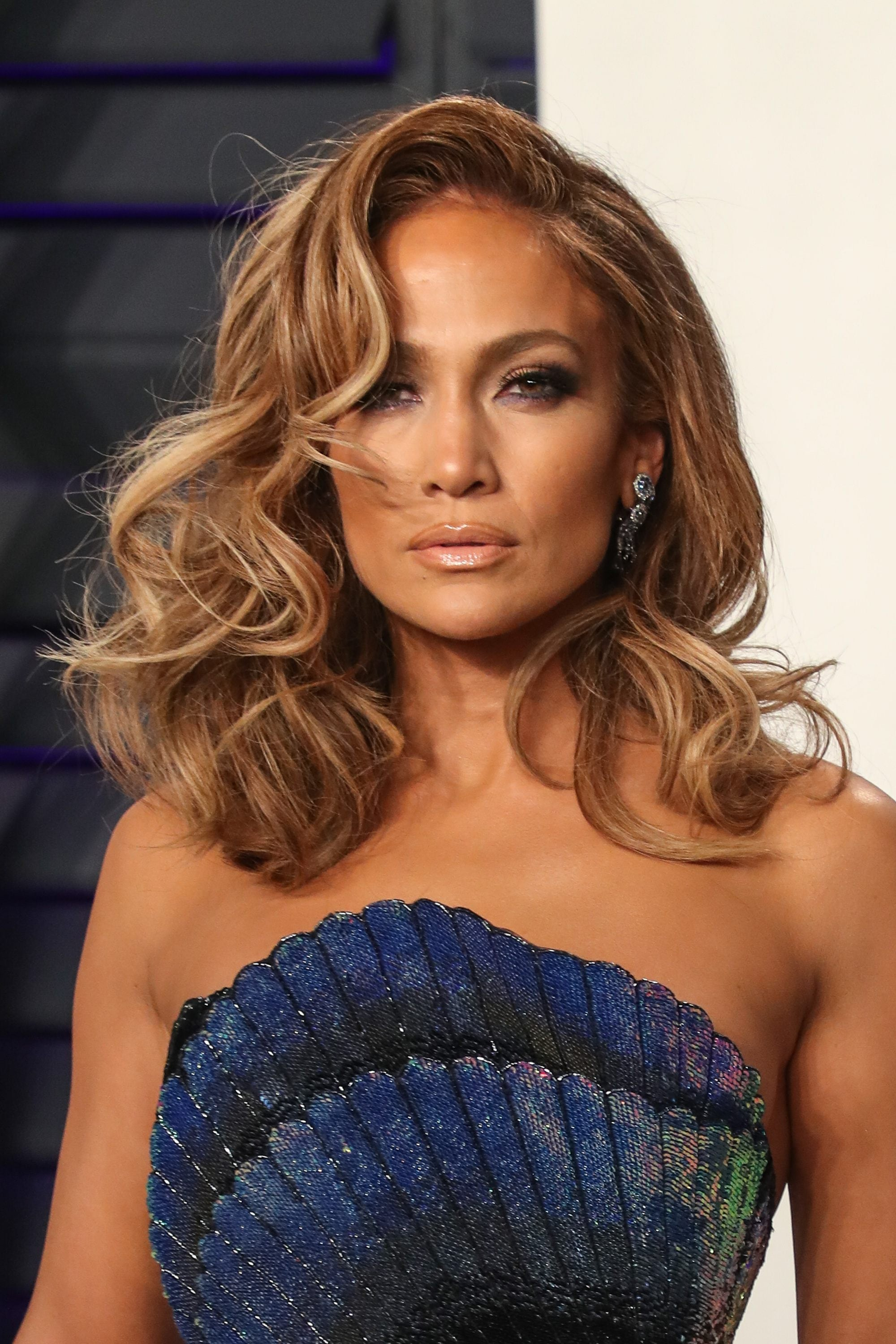 Highlights and lowlights: Jennifer Lopez with medium length curly hair with side fringe.