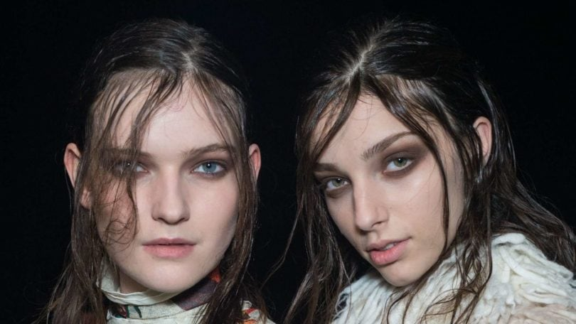 Shampoo for greasy hair: Two brunette models backstage at just cavalli fw15 show with wet look greasy hair with dark eye make-up