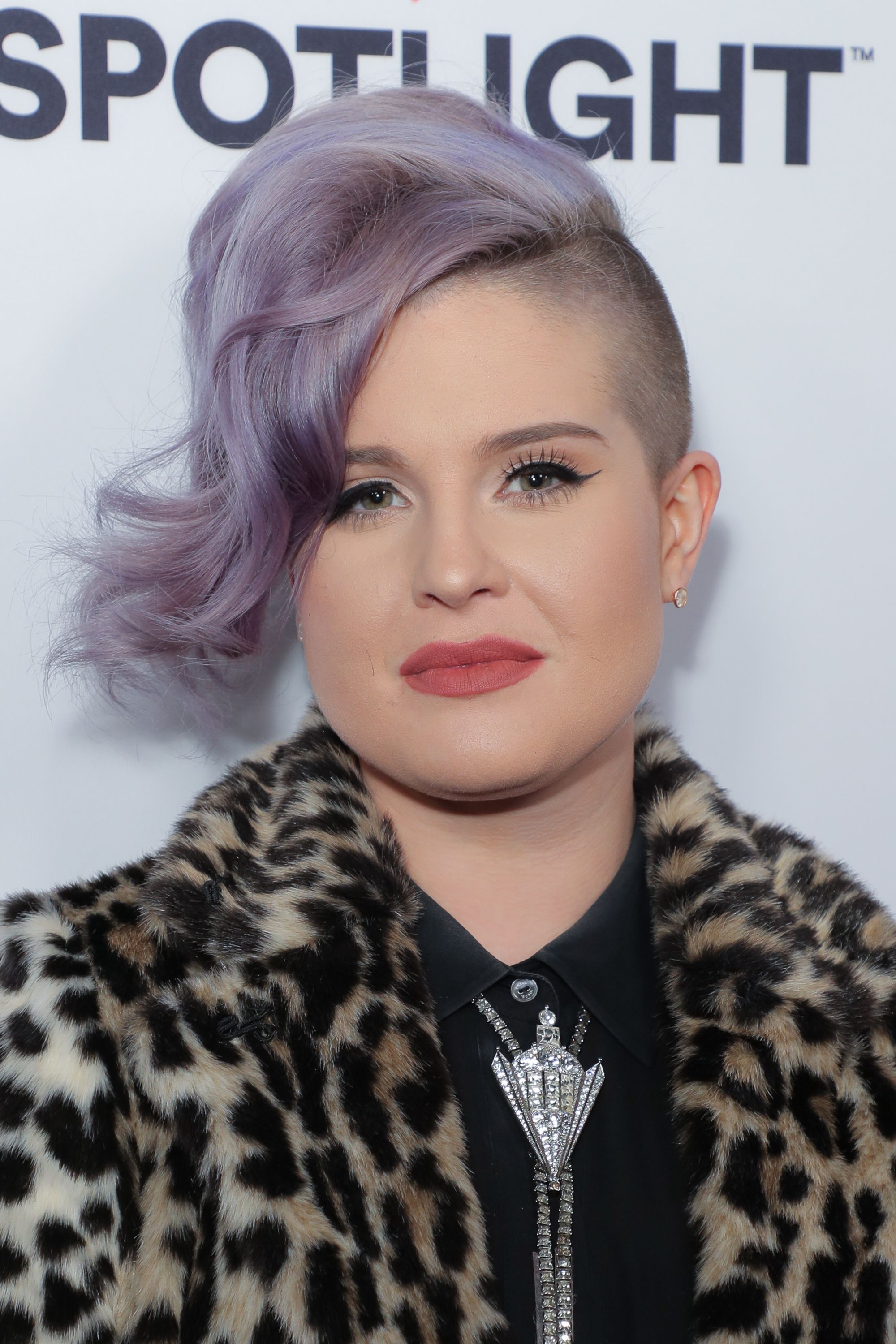 kelly osbourne with lilac curled short hair with one shaved side, wearing a leopard print fur coat
