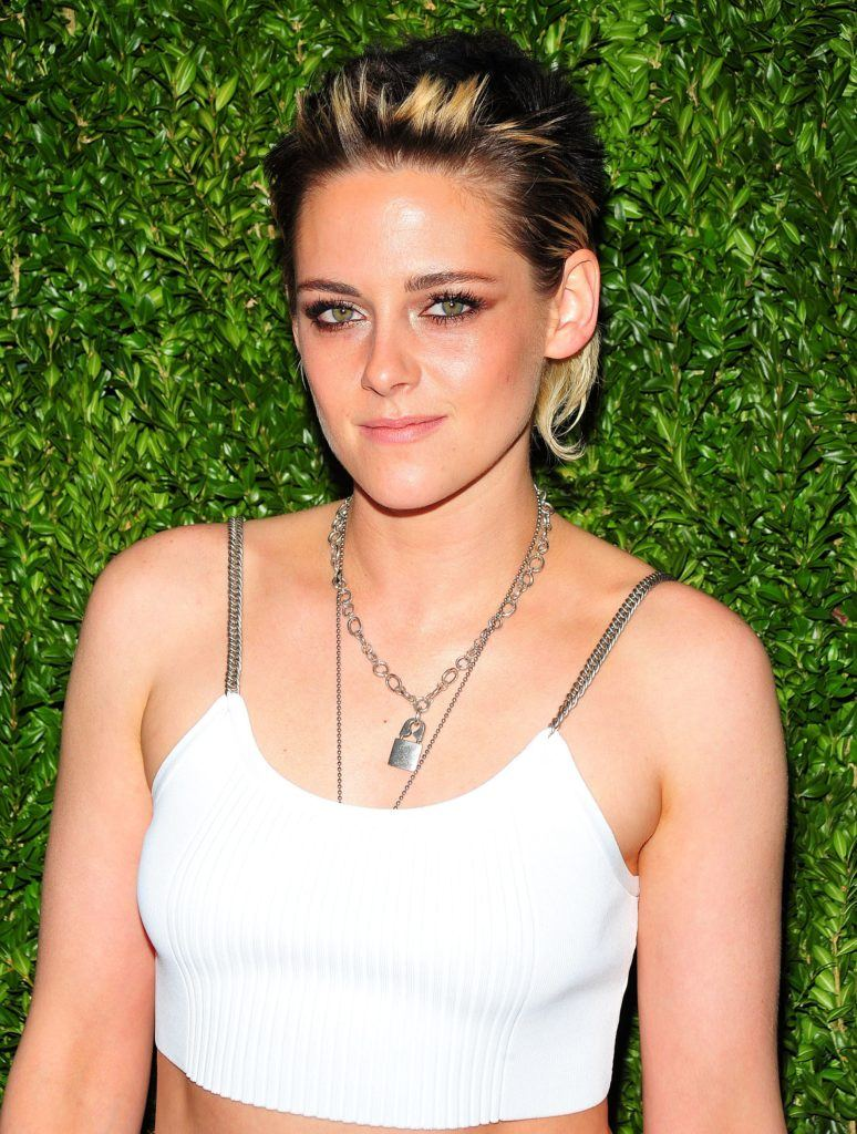 actress kristen stewart wearing a white crop top with her short brunette hair with blonde highlights in a grown out mullet style