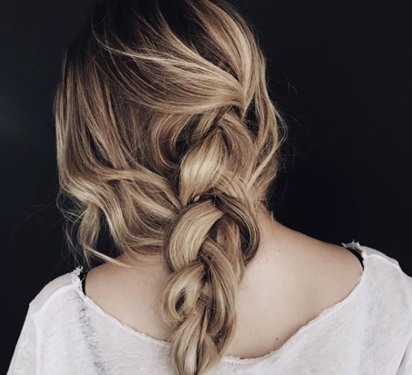 close up Instagram shot of with loose braided low ponytail, wearing all white and posing in studio