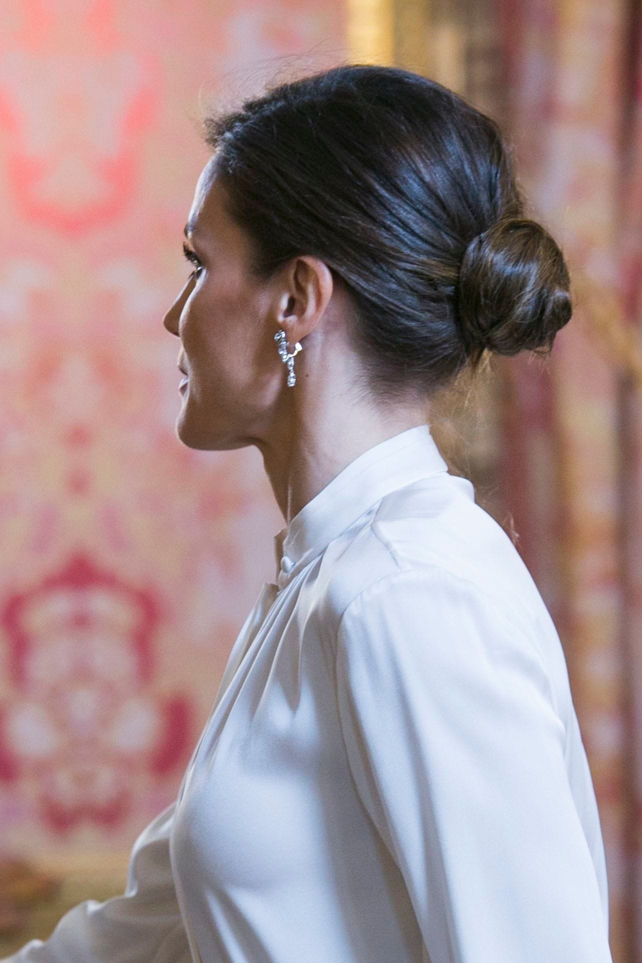 Wedding guest hair: Side shot of a woman with dark brown hair styled into a low, polished bun wearing a white blouse