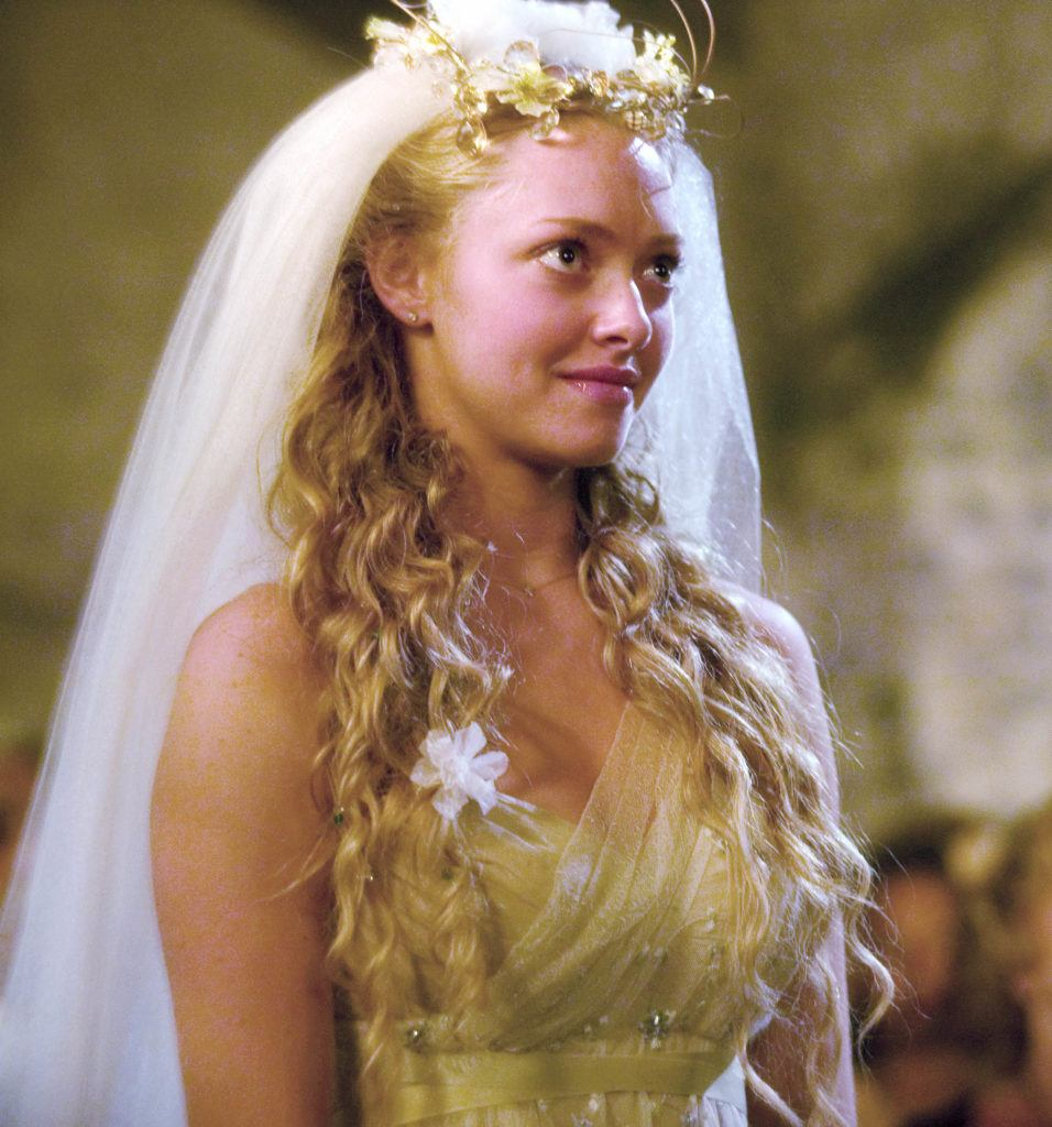 close up shot of amanda seyfried as sophie, with half up curly hairstyle, viel and flowers, on the set of mamma mia